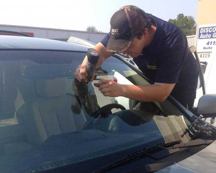 мастер ремонтирует скол на лобовом стекле